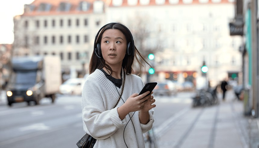 adapt-100---young-woman-on-sidewalk-with-headphones-on